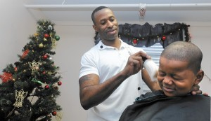Odenton, MD-12/23/13-Odenton barber Robert Cradle cuts Isaiah DuBose's hair. DuBose is 5. Cradle cuts hair for homeless students who live in Sarah's House, a homeless shelter across from Fort Meade. He has launched a foundation that raises money to provide grooming and hygiene to the underprivileged in Anne Arundel County. Photographer}/Baltimore Sun, #5625.